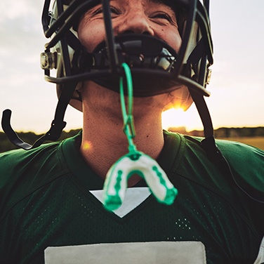 boy with football gear and mouthguard
