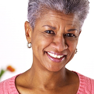 Older woman with pink shirt and earrings smiling